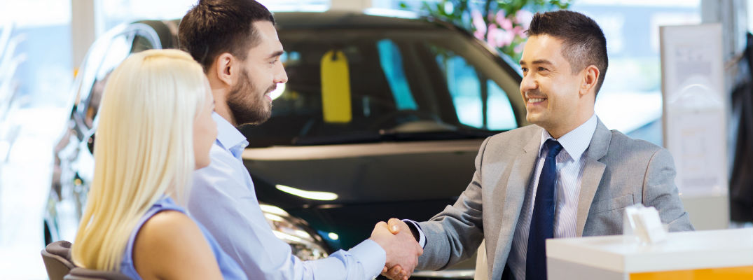 A young couple completing a sale with a dealership respresentative