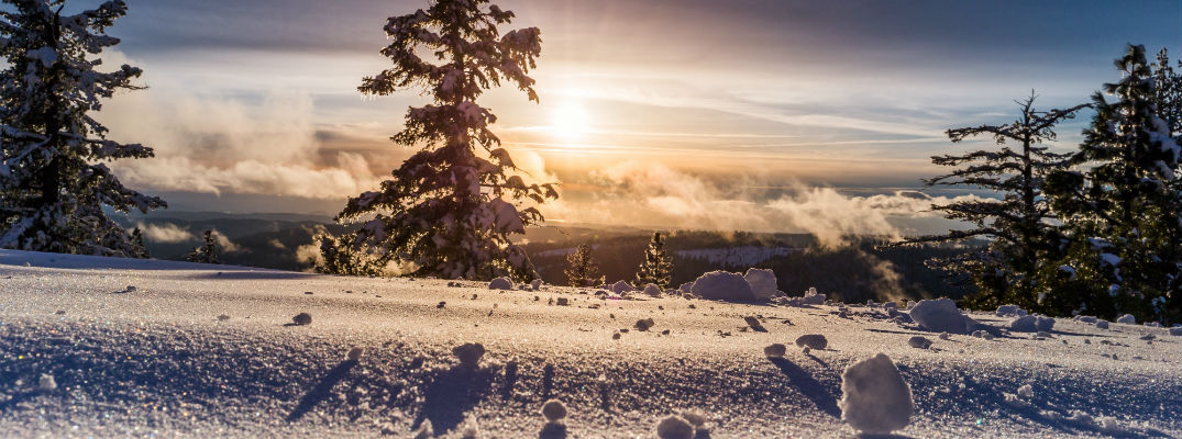A photo of a winter landscape with sun rising in the background