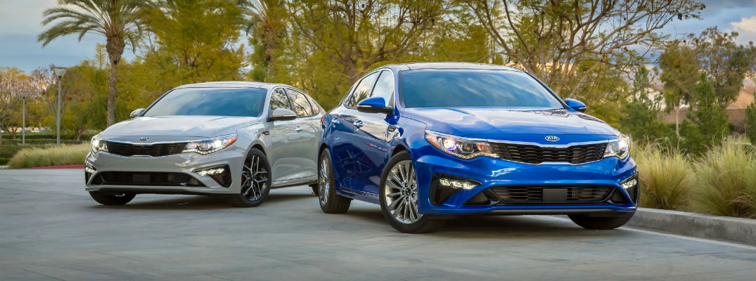 A photo showing two versions of the 2019 Kia Optima sitting side by side.