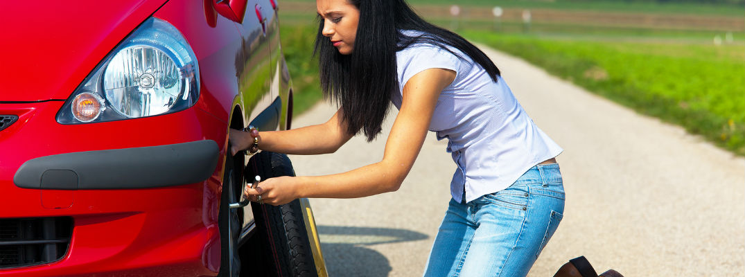 A stock photo of a young woman changing a flat tire.