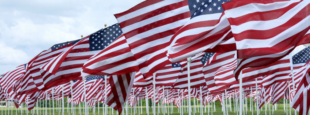 A stock photo of American flags lined up for a Memorial Day ceremony.