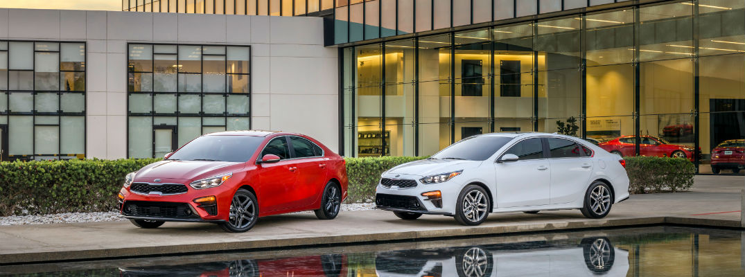 A photo of two 2019 Kia Forte sedans parked in front of a building.