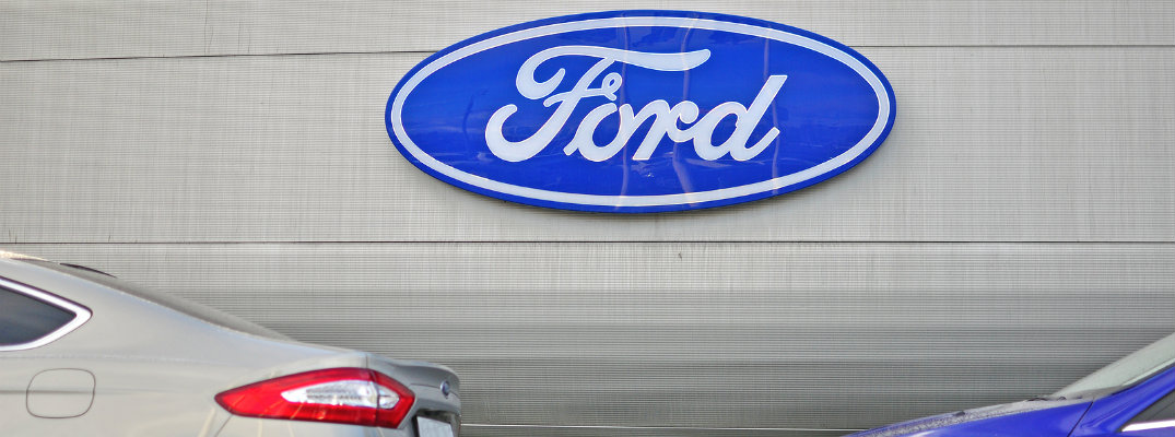 Ford logo on silver background with two Ford models slightly in frame