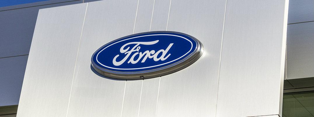 Exterior shot of Ford dealership with logo prominent in center