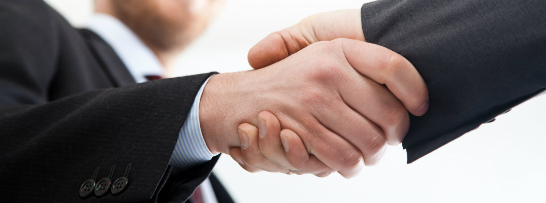 Two businesspeople wearing suits and shaking hands