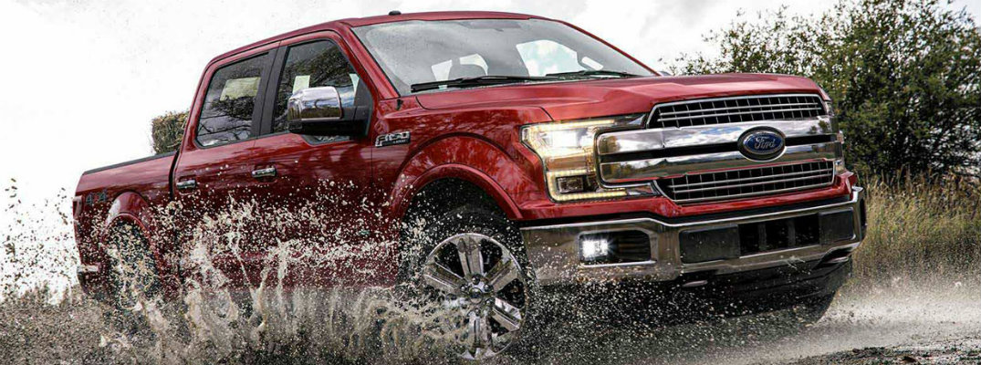 Red 2018 Ford F-150 truck driving through mud in overcast weather
