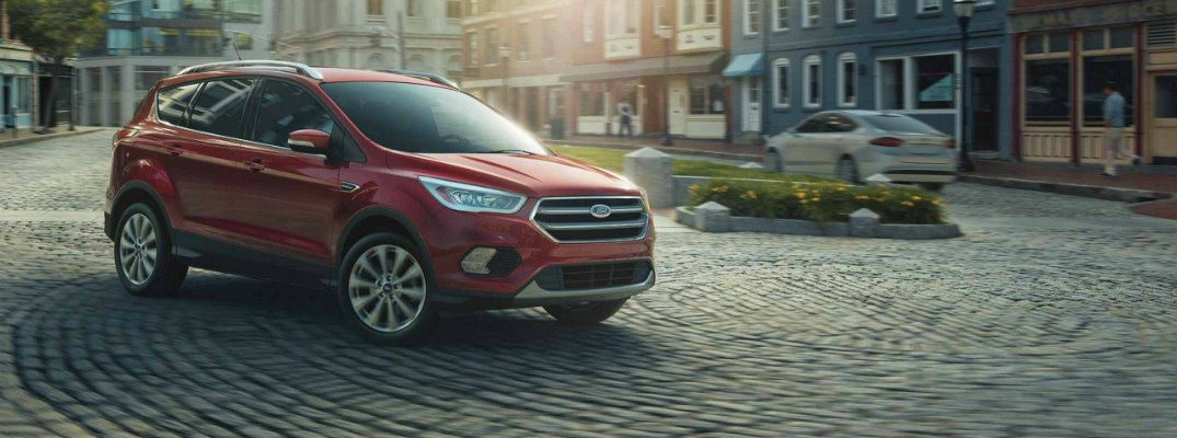 Red 2018 Ford Escape Titanium driving down brick-lined city road