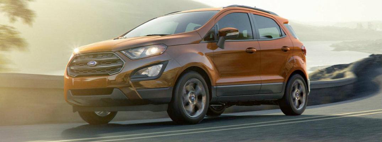 Burnt orange 2018 Ford EcoSport driving at dusk