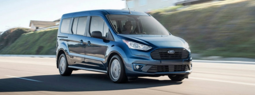 Blue 2019 Ford Transit Connect driving down residential road with houses in background