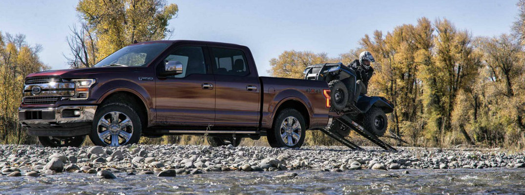 2018 Ford F-150 SuperCrew pickup parked on pebbly ground with trees in background