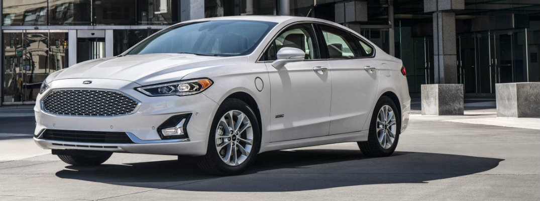 Profile view of white 2019 Ford Fusion driving on city street