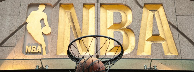 Gold NBA logo with basketball going through hoop underneath