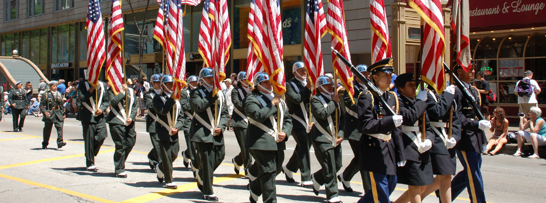 Uniformed military men and women holding American flags while marching in parade
