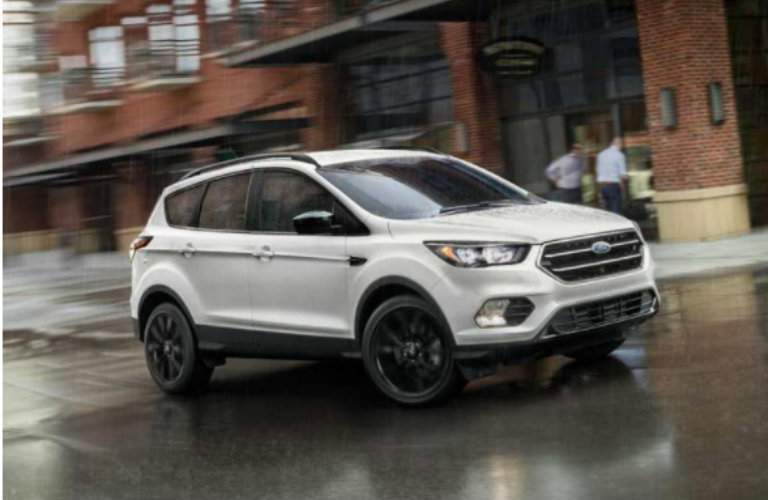 White 2018 Ford Escape driving on rainy city road
