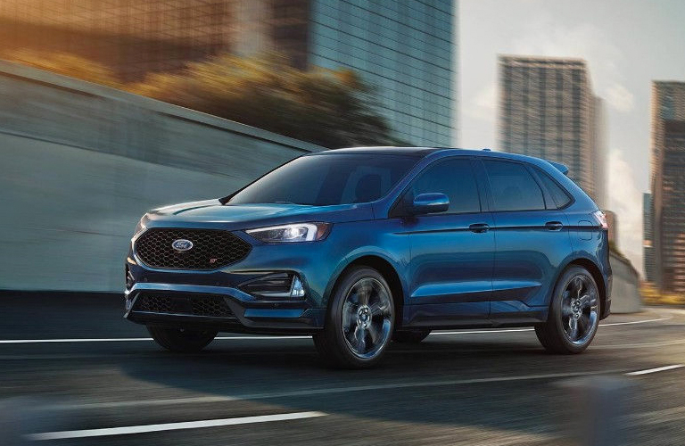 Blue 2019 Ford Edge driving through city