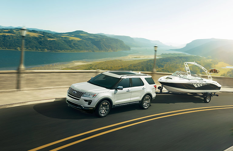 White 2019 Ford Explorer towing boat on waterfront road