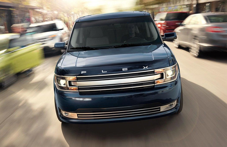 Front grille and headlights of blue 2019 Ford Flex driving in city