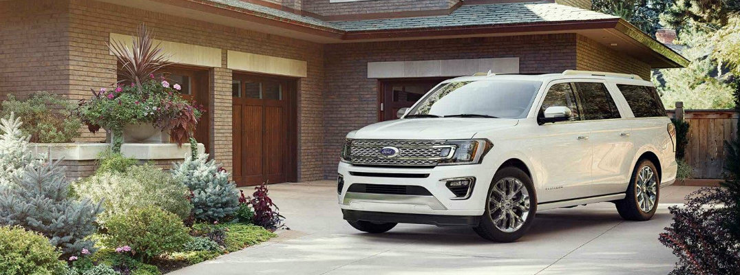 White Ford Expedition parked in front of modern-styled house