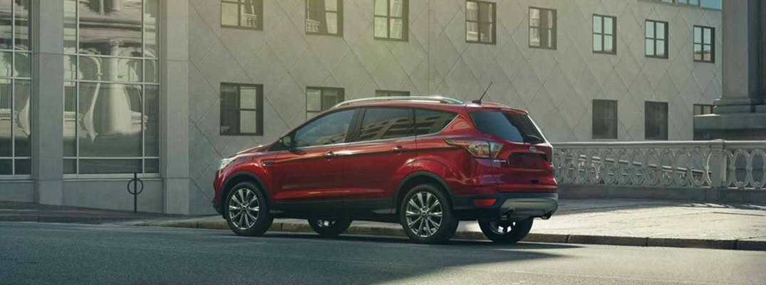 Profile view of red 2019 Ford Escape parked on city curb