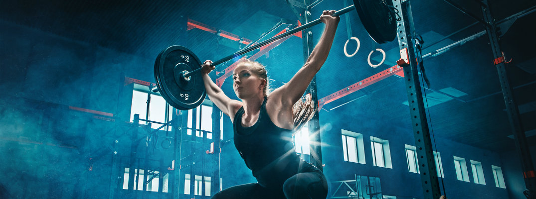 Young woman doing overhead squat inside gym