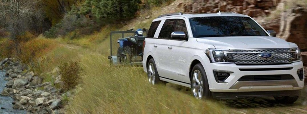 White 2019 Ford Expedition towing ATV on waterfront trail
