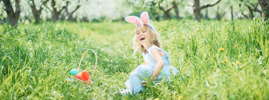 girl sitting in grass laughing with easter eggs