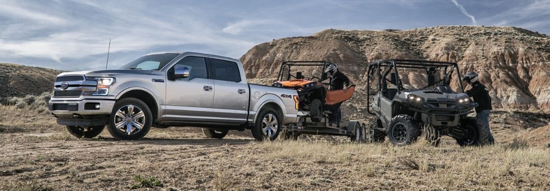 Exterior view of a silver 2020 Ford F-150 towing a trailer hauling UTVs