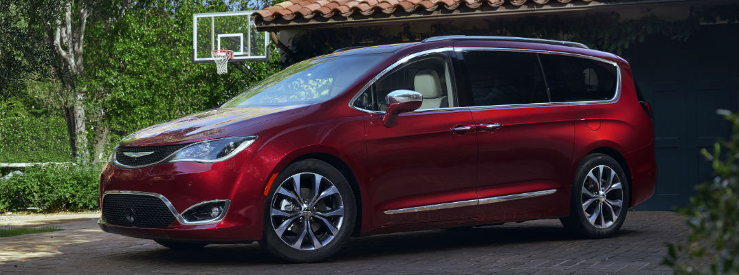 A left profile view of a red 2018 Chrysler Pacifica in a driveway