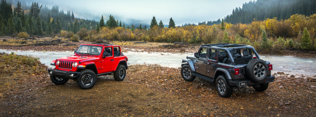 A side-by-side photo of a two- and four-door version of the 2018 Wrangler on display next to a river