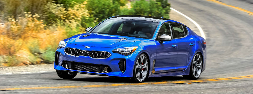 A photo of a blue 2018 Kia Stinger driving down the road