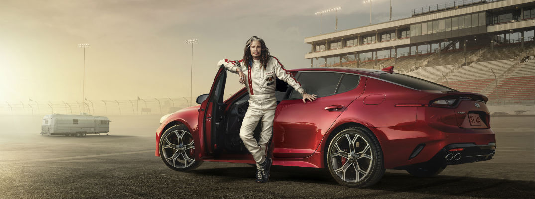 A photo illustration of Steve Tyler from Aerosmith standing in front of a red 2018 Kia Stinger on a race track.
