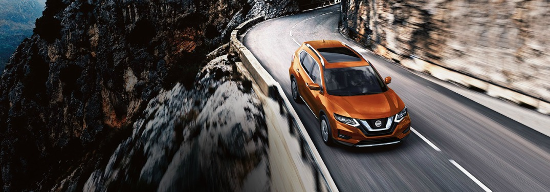 orange 2018 Nissan Rogue driving in the mountains
