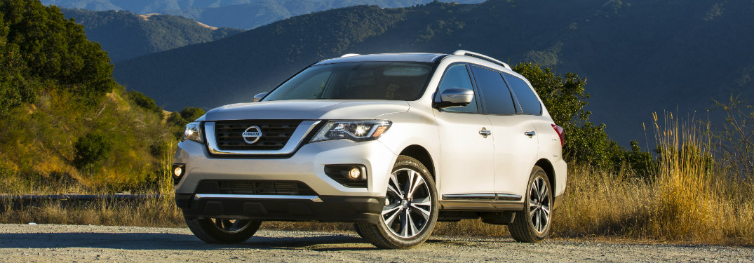 white 2018 nissan pathfinder in desert with bushes and mountains surrounding it