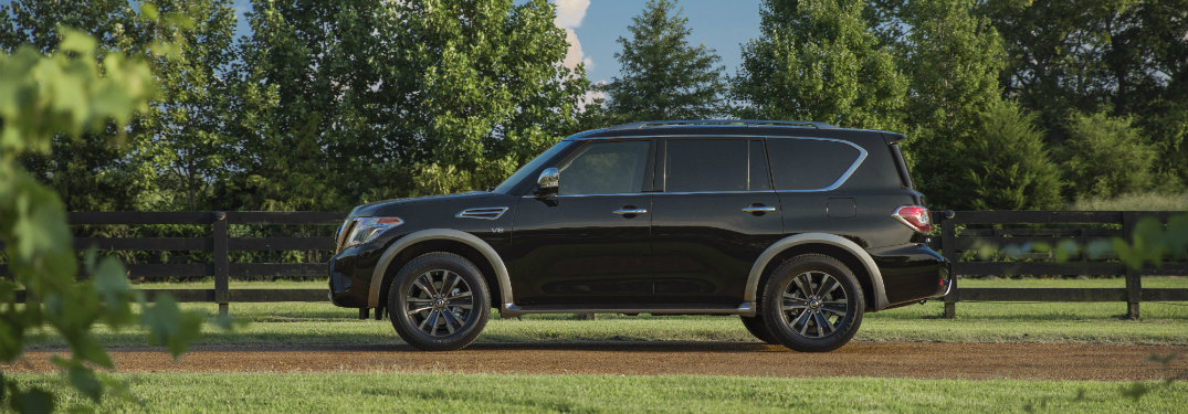 side view of blue 2018 nissan armada on dirt trail surrounded by grass and trees
