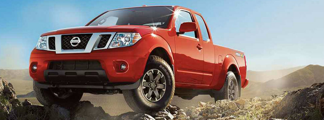 View of red 2018 Nissan Frontier driving over rocky surfaces