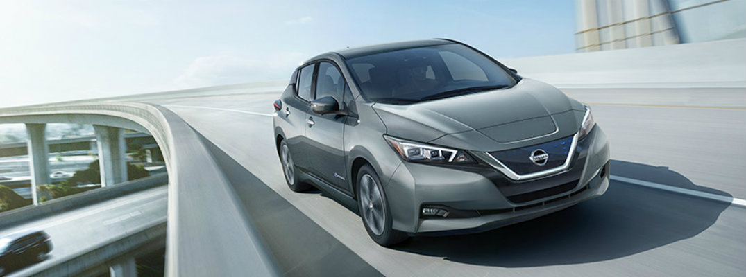 Exterior view of silver 2018 Nissan LEAF driving down an elevated highway