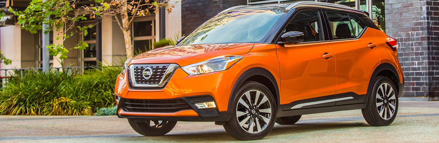 Exterior view of an orange 2018 Nissan Kicks parked outside a building