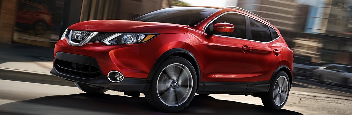 Exterior view of a red 2018 Nissan Rogue Sport driving down a city street