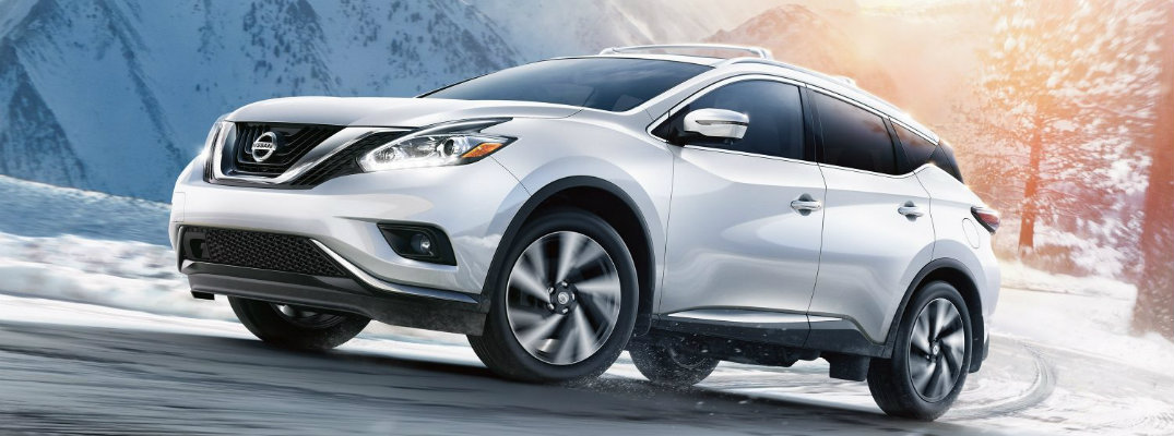 Exterior view of a silver 2018 Nissan Murano driving on a road during the winter