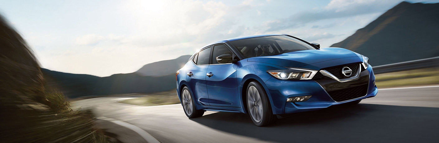 Exterior view of a blue 2018 Nissan Maxima driving down a two-lane highway with mountains in the background