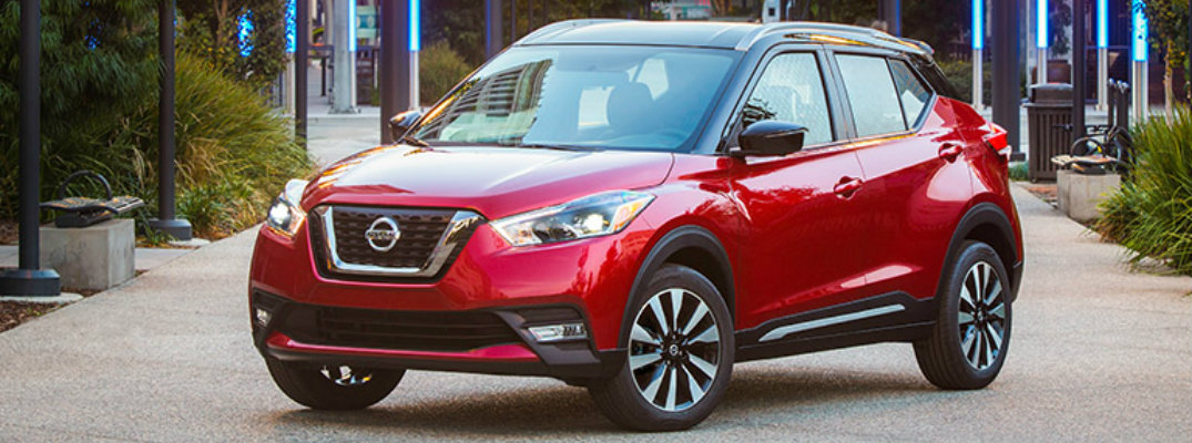 Exterior view of a red 2018 Nissan Kicks parked in a park during the day