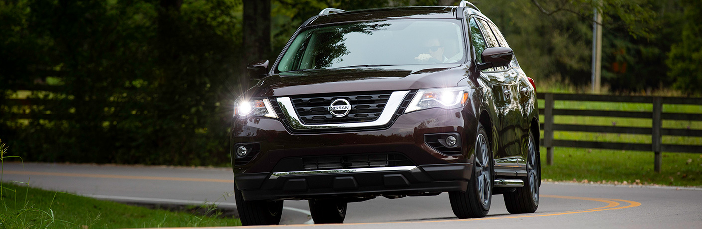Exterior view of a maroon 2019 Nissan Pathfinder driving down a two-lane country road