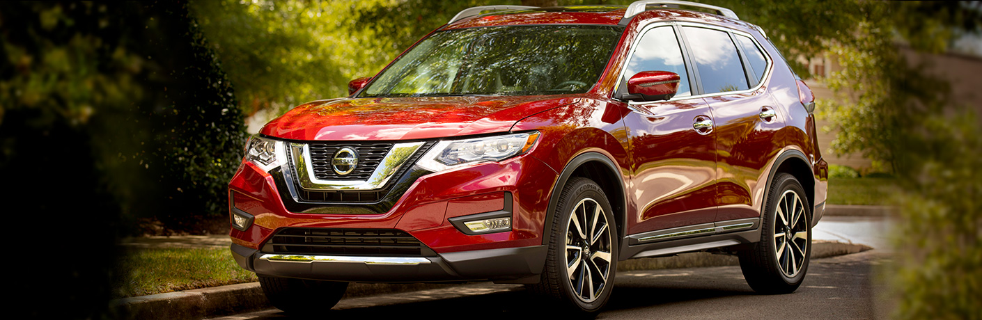 Exterior view of a red 2019 Nissan Rogue parked on a suburban street