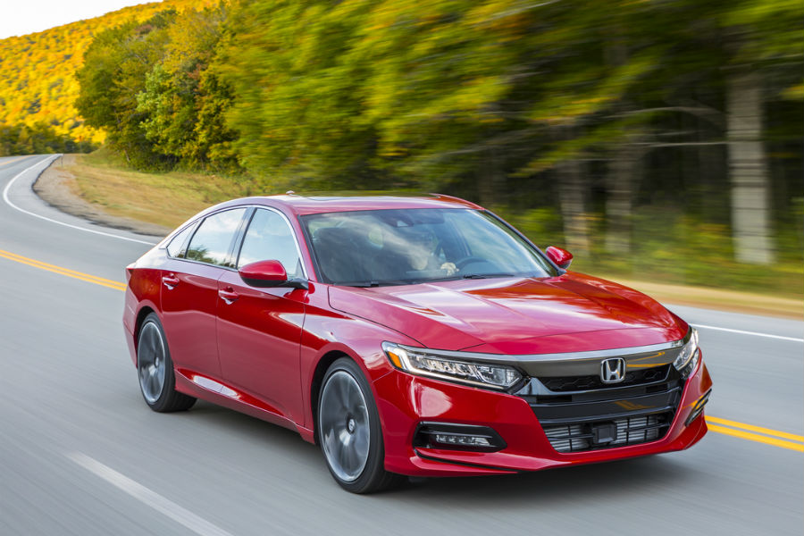 2018 honda accord in bright red driving on country road in front of tree-lined forest