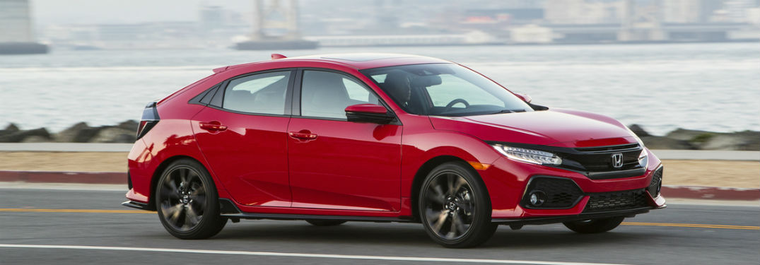 2018 honda civic hatchback driving on side of road near coast
