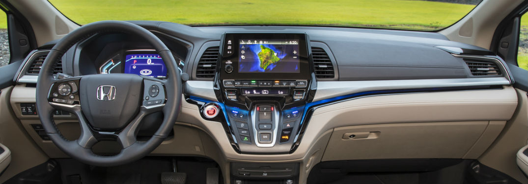 interior dashboard in 2018 honda odyssey seen from front center in front of picturesque grassy scene