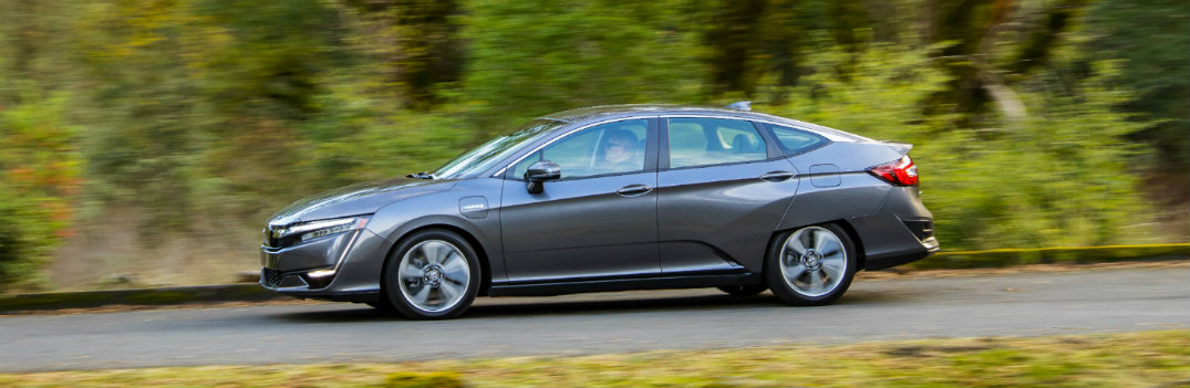 2018 Honda Clarity Plug-In Hybrid driving down a road by a forest