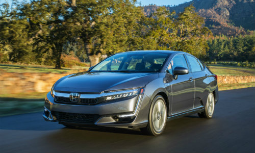 2018 Honda Clarity Plug-In Hybrid driving with grassy mountain background