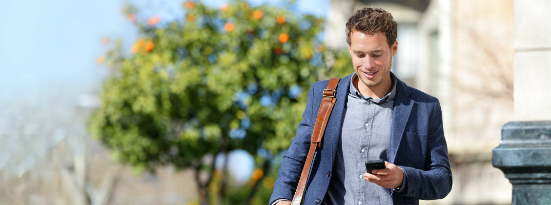 man walking to work in the sunny afternoon while looking at his smartphone