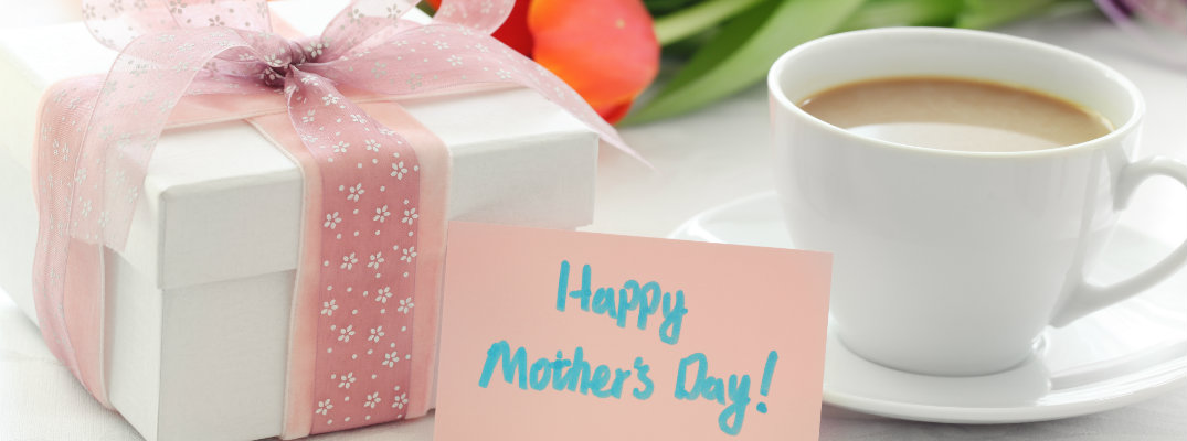 happy mother's day card next to a cup of coffee, flowers, and a wrapped gift